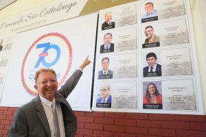 Deputado João Campos apontando para parede onde aparece a sua foto em mural