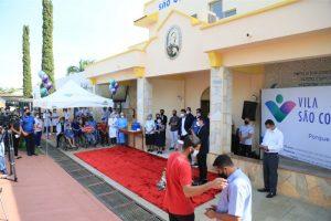 Pessoas à frente da capela da Vila São Cottolengo aguardando início da vacinação