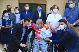 Paciente de cadeira de rodas segurando cartão de vacinação entre prefeito de Trindade e diretor da Vila São Cottolengo