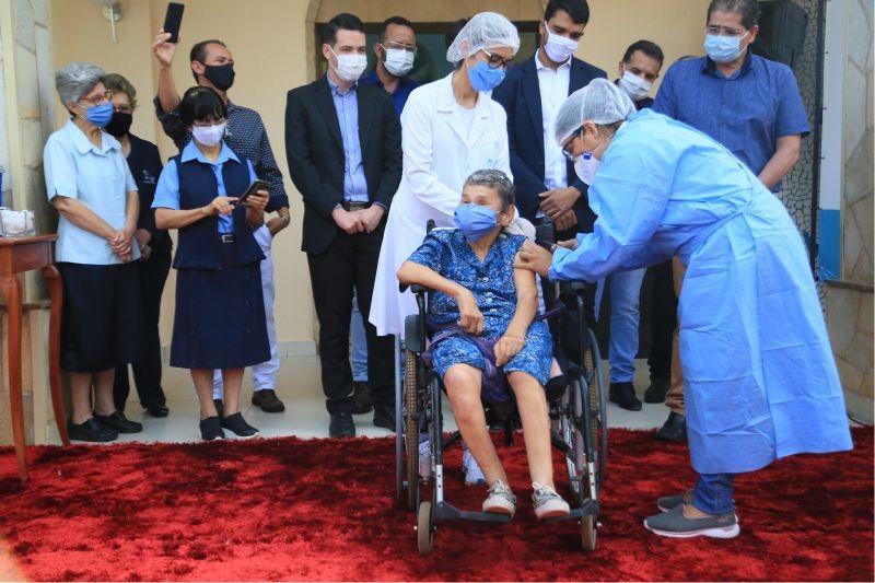 Paciente de cadeira de rodas ao centro recebendo a vacina com duas profissionais da saúde